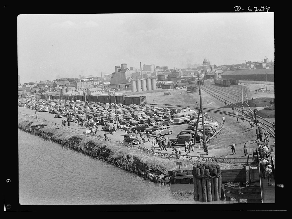 Production. Submarines. Before gasoline rationing, in a Midwest shipyard's parking lot. Today, this same view would probably show fewer cars, as workers all over the country have formed car pool clubs to save tires and gasoline