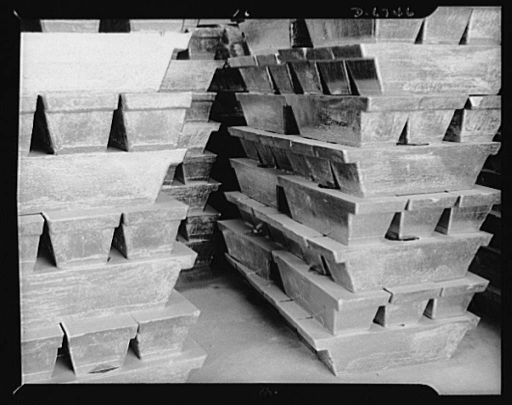 """Production. Tin smelting. """"Bars"""" of pure tin are stacked in the warehouse of a Southern smelter to await shipment for war uses. Each bar weighs about eighty pounds and has a value of about forty-one dollars and sixty cents at the present price of fifty- two cents per pound. This tin, made from South American ore, serves many needs of the United Nations"""