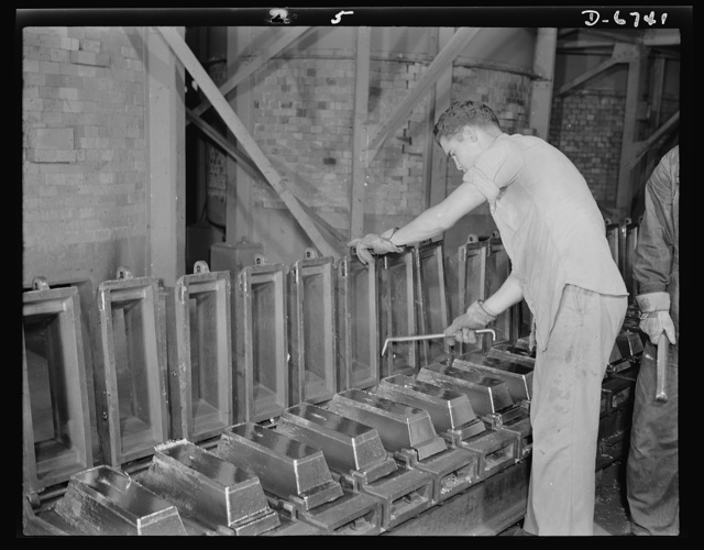 """Production. Tin smelting. """"Bars"""" of pure tin are trimmed and cleaned before removal from the molds in which they were formed in a Southern smelter. All the trimmings are returned to the """"pot boilers"""" for remelting. The plant, finest and most modern in the world, extracts the pure metal from South American ore"""