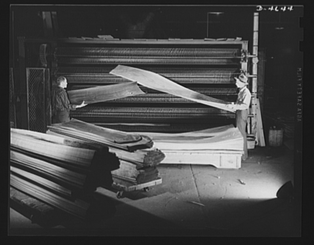 Production. Veneer for aircraft and other war essentials. A strip of walnut veneer that will be used in a panel of a combat plane comes from the textile dryer of a Midwest plant. This operation reduces the moisture content to about eight to ten percent. Sheets are stacked in exact sequence just as they come off the knife slicer from the log. Louisville, Kentucky