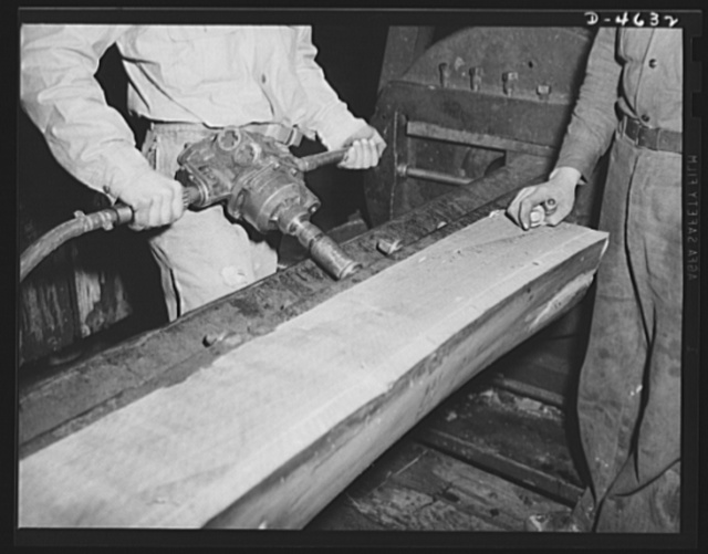 Production. Veneer for aircraft and other war essentials. A walnut half log is bolted on the stay log of a machine that will cut it smoothly and with great precision into veneer for our combat planes. Louisville, Kentucky