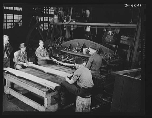 """Production. Veneer for aircraft and other war essentials. Veneer for combat planes. In the """"half-round method,"""" a half log, after being heated in water to the proper temperature, is bolted on a stay log and revolved against a stationary knife. The sheets, as they fall from the knife, are stacked in proper sequence just as they were in the log. Louisville, Kentucky"""