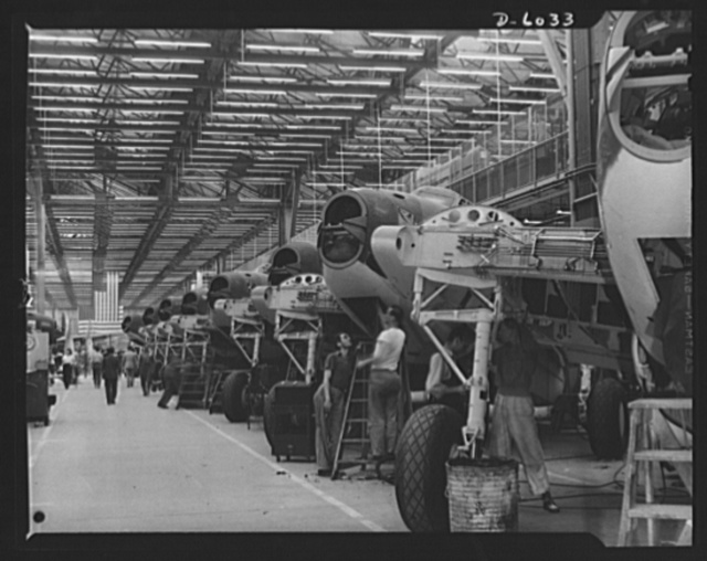 """Production. Ventura bomber. Along the well-lighted length of the """"MacArthur Boulevard"""" in a large Western aircraft plant are the assembly lines from which a steady stream of Ventura bombers is pouring. This section of one of the lines gives some idea of the rate at which production is moving. Vega Aircraft Corporation, Burbank, California"""