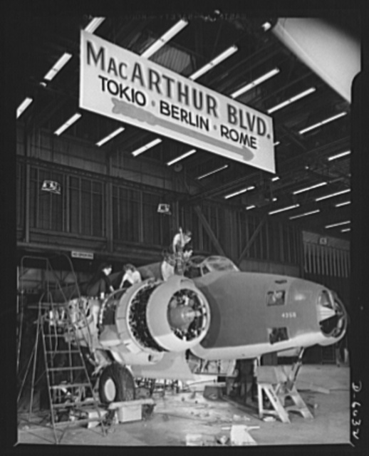 """Production. Ventura bombers. On """"MacArthur Boulevard"""" in a large Western aircraft plant. Ventura bombers are rolling off an assembly line that hums every hour of the day and night. As the sign points out, this assembly line is the real starting point of many warlike trips to Tokyo, Berlin, and Rome. Vega Aircraft Corporation, Burbank, California"""