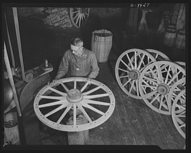 Production. Wagon wheels. Revival of a dying art. A wheelwright in a Southern wagon plant operates a machine to insert bolts in the felly, or outer wooden rim of the wheel, prior to the fitting of the metal tire