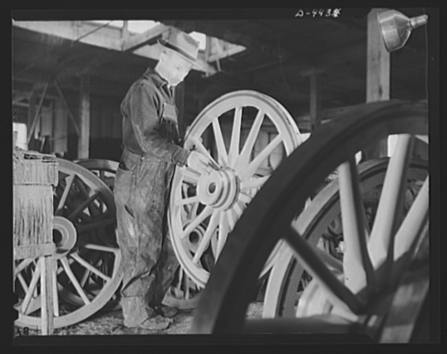 Production. Wagon wheels. Revival of a dying art. Applying the finishing touches to a completed wagon wheel in the painting room of a Southern wagon wheel company which is swamped with orders because of the rubber shortage