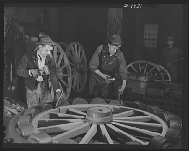 Production. Wagon wheels. Revival of a dying art. Fitting the steel tire to the wagon wheel assembly in the plant of a Southern wagon company which is experiencing a business boom because of the rubber shortage