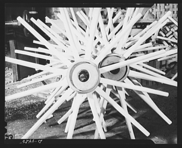 Production. Wagon wheels. Wagon wheels in the making. Spoke and hub assemblies are stocked at a Southern wagon plant for the next operation, the fitting of the felly, or wooden rim