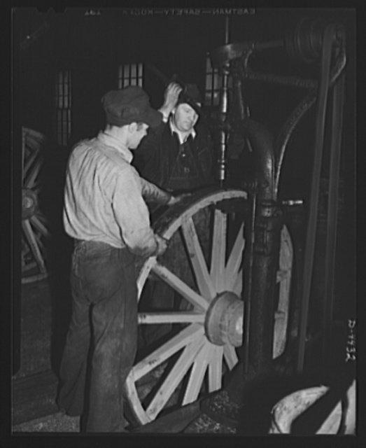 Production. Wagon wheels. Wagon wheels in the making. Workers in a Southern wagon plant countersinking steel tire which has been attached to wheel assembly. Wagon wheel making is having a boom business because of the rubber shortage