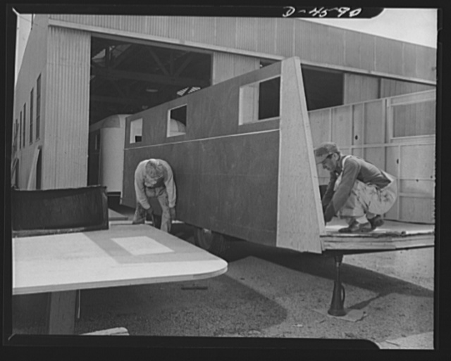 Production. War housing trailers. A complete side assembly of a war housing trailer is set in place and secured at the Los Angeles plant of Western Trailer Company. At this stage, the trailer chassis is held on jacks to give stability and to make fitting of sections fast and accurate