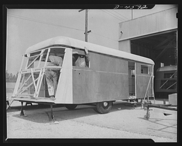 Production. War housing trailers. A war housing trailer takes shape at the Los Angeles plant of Western Trailer Company. Frame members have already been installed at the rear of this trailer, and the top is set in place. A new chassis is already in place at the right, ready to receive stringers