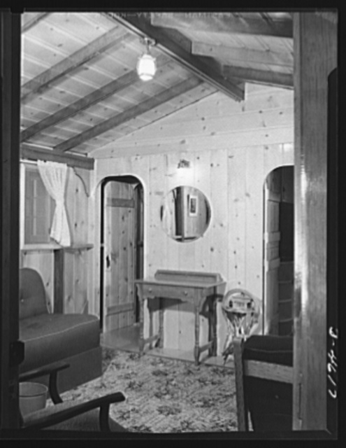 Production. War housing trailers. Knotty pine walls and beamed ceilings give the prefabricated Westcraft home a neat, cozy interior. The door in the background opens into a bathroom, equipped with full-size standard fixtures, including shower. The house may be assembled in four to six hours by inexperienced men, in half the time by skilled carpenters. It may be dismantled in even less time for removal to another site. It is made by Western Trailer Company of Los Angeles, builders of the war housing trailers