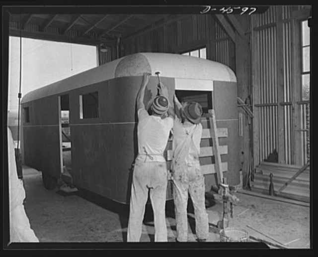 Production. War housing trailers. Small corner sections are installed on a war housing trailer nearing completion in the Los Angeles plant of Western Trailer Company. Clamps hold big pieces of Masonite in place while the glue dries