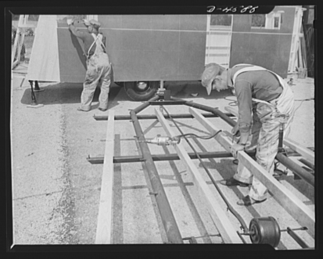 Production. War housing trailers. Stepped-up production of war housing trailers caused an assembly line to overflow into a plant yard at both ends. View of the spill-over assembly line of Western Trailer Company at Los Angeles. Chassis seen here have been much simplified over former types, using a minimum of steel. Wood stringers replace metal formerly employed. The trailer in the background has sides in place and is now ready to hit the inside assembly line