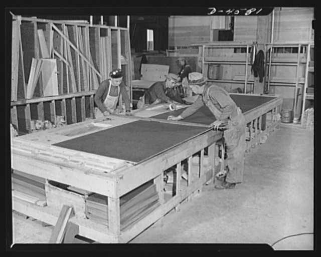 Production. War housing trailers. The side of a war housing trailer nears completion on a table-top jig at Western Trailer Company's plant in Los Angeles. Exceptional strength is secured through built-up construction of Masonite over plywood with a casein bond. The side is secured to spacers with drive screws