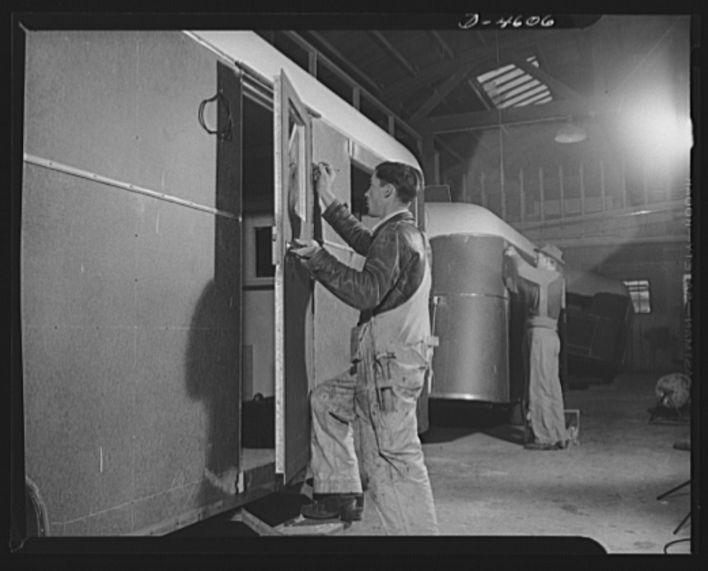 Production. War housing trailers. The trailer door is the last major assembly to be fitted to a war housing trailer at the Los Angeles plant of Western Trailer Company. The worker in the background is installing clearance light fittings. The vehicle is now ready for the final paint job