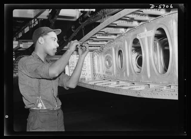 Production. Willow Run bomber plant. A Negro worker at the giant Willow Run bomber plant installs screws in one end of a wing segment