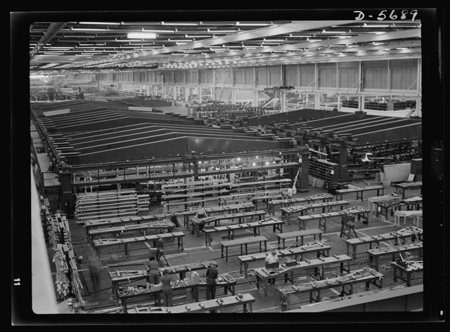 Production. Willow Run bomber plant. A small part of the world's largest one-story war production plant, the giant bomber factory at Willow Run, Michigan. Fixtures in background hold bomber wings during assembly. Ford plant, Willow Run
