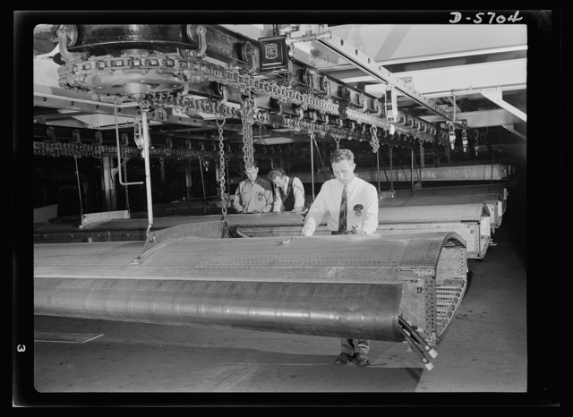 Production. Willow Run bomber plant. Checking almost-completed wing structure with blueprints, engineers at the great Willow Run bomber plant determine next steps to be taken before the wings leave the assembly line. Ford plant, Willow Run