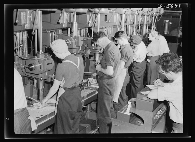 Production. Willow Run bomber plant. Drill press lineup, 1943 style. Both men and women man the machines which are turning out parts for America's bomber planes at Willow Run, Michigan. Ford plant, Willow Run