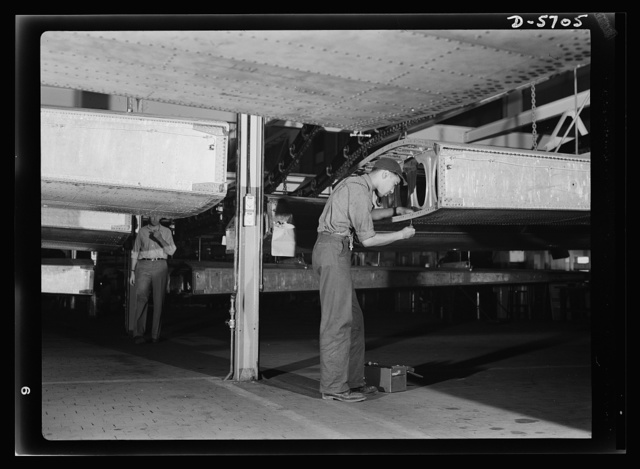 Production. Willow Run bomber plant. Negro worker at Willow Run installs screws in wing segment of a bomber. Note underside of wing, above. Ford plant, Willow Run