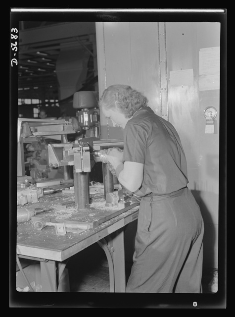 """Production. Willow Run bomber plant. One of the many women employed at the giant Willow Run bomber plant operates a drill to bore holes in the """"Y"""" section of a supercharger bracket. Ford plant, Willow Run"""
