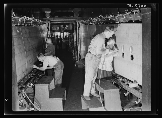 Production. Willow Run bomber plant. The outer wing panel of a bomber undergoes assembly in the giant Willow Run plant. When finished, this section will be removed and cranes will install another section in the fixture. Ford plant, Willow Run
