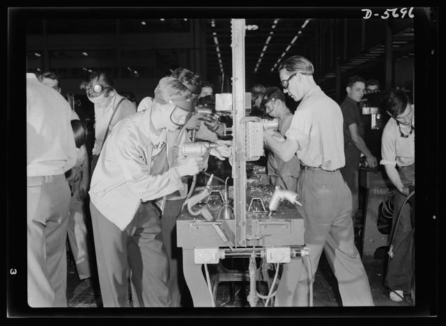 """Production. Willow Run bomber plant. They're learning a fourth """"R"""" at this school, and one that's highly important to the war effort. Young men in the Willow Run bomber plant attend a riveting school before going to work on the assembly lines. These """"schoolrooms"""" are right in the plant proper; classes are held in many types of work. Ford plant, Willow Run"""