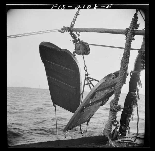 """Provincetown, Massachusetts. Aboard the Frances and Marion, a Portuguese drag trawler, fishing off Cape Cod. """"Doors,"""" which when lowered, slide over the bed of the ocean like sled runners, dragging behind them the purse seine which scoops up miscellaneous fish, rocks, crabs, lobsters, and a great deal of slime"""