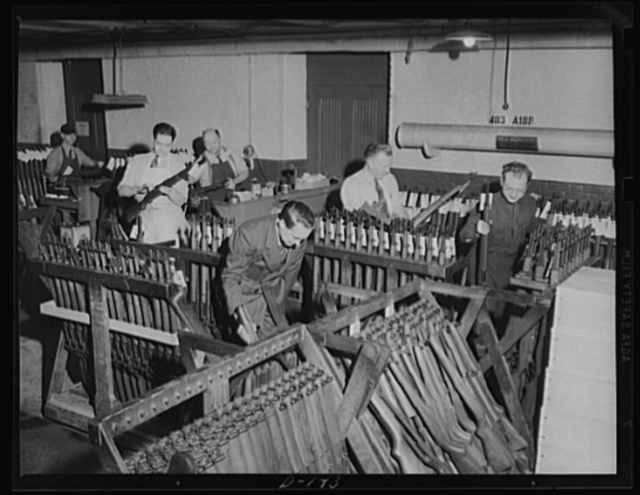 Putting them together. A corner of the assembly room at an armory, where war workers are putting together the parts which make up a Garand rifle