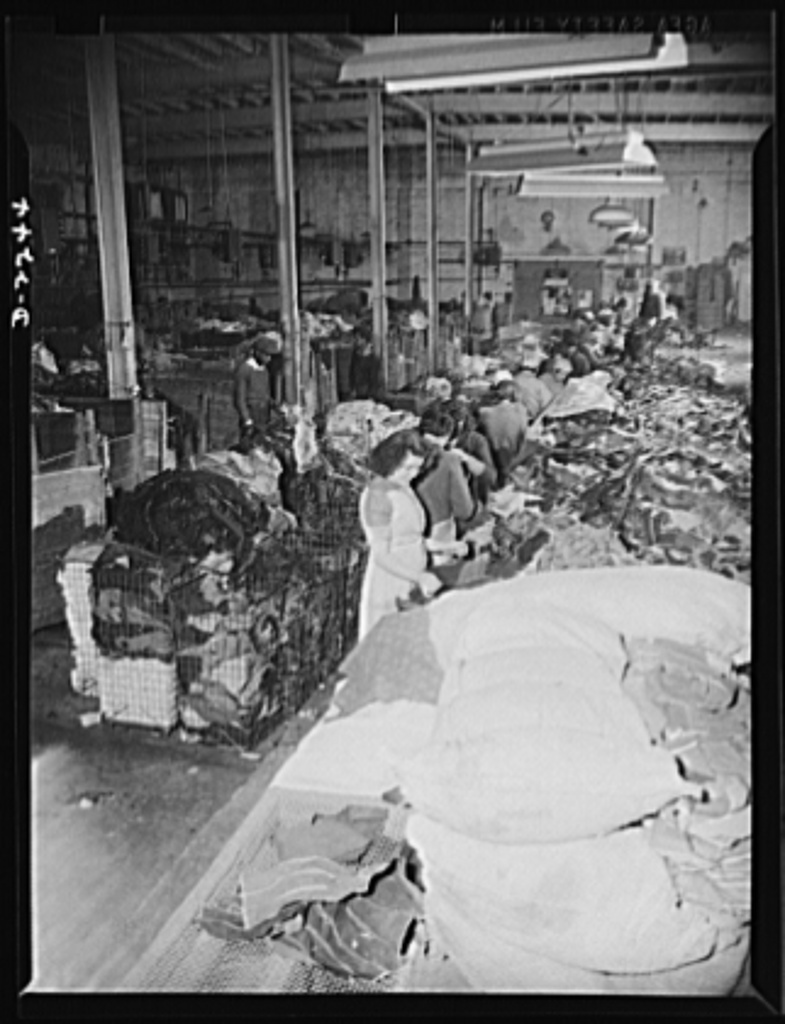 Rags. Collection and processing. A portion of the sorting room in a large Eastern rag processing plant. In this room new rag remnants, consisting chiefly of cuttings received from clothing factories, are sorted. The rags are classified and separated according to the type of cloth; colored rags are graded according to the ease with which they can be bleached. The baskets in back of the women are filled with rags that have been sorted and classified. The women work in teams of two; it takes a team about two hours to sort the rags in one full bale. In another part of the plant, a room of the same size and general appearance as this is used for sorting used rags. Shapiro Company, Baltimore, Maryland