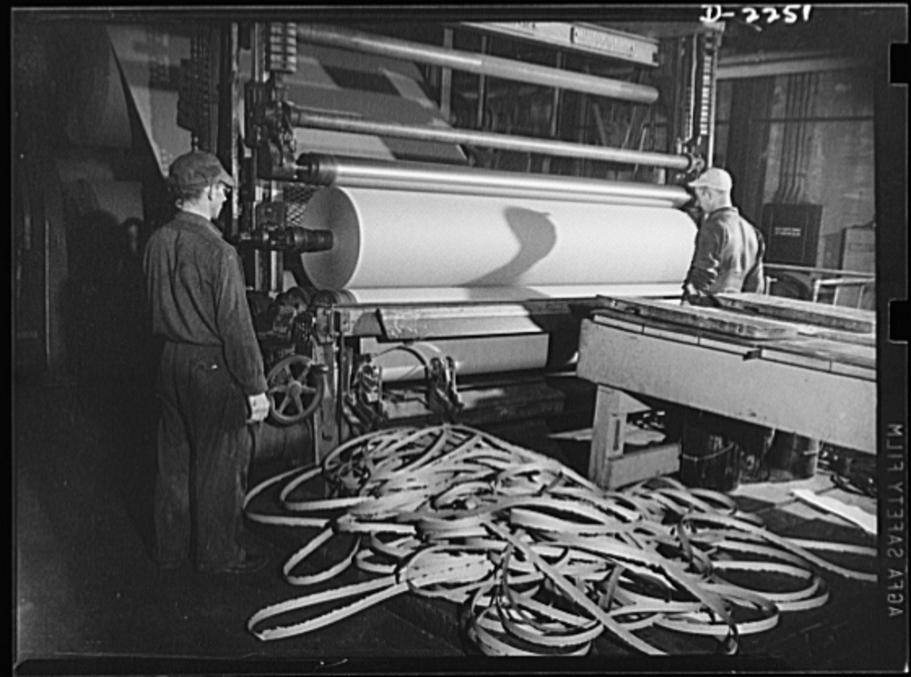 Rags. Collection and processing. Roofing being wound into rolls at a Maryland plant. Rags and waste paper are used extensively in the manufacture of this material. The strips on the floor are trimmings which are left after the edges of the roll have been made even
