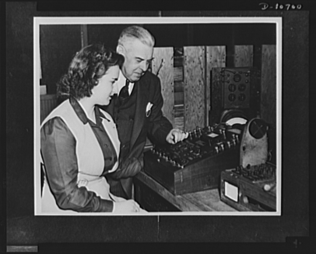 """Rochester, New York. Madison E. Butler, assistant chief inspector for the Stromberg-Carlson Telephone Manufacturing Company, who developed a visual-lamp indicator to test field telephone switchboards and which the U.S. Army Signal Corps claims has saved the equivalent of almost thirty-seven years work, shown at his testing instrument. He received one of the first five """"Citations of Individual Production Merit"""" for his idea which has an outstanding effect on the entire war effort"""