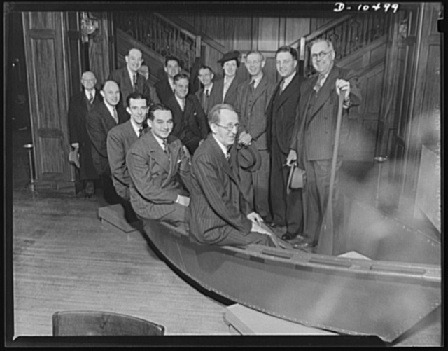 """Sagebrush sailors"" at war clinic. Contractors' and manufacturers' representatives dubbed themselves ""sagebrush sailors"" as they posed in an Army assault boat on display at the war clininc being held at the Whitcomb Hotel in San Francisco. Potential sub-contractors were invited to attend the clininc on ""Nevada Day,"" sponsored by the contract distribution branch of the production division, War Production Board (WPB), to negotiate for war contracts. Front row, left to right, are: W.H. Medley, O.M. Dahl; Jean Putz; Harmon Walker and Ralph Mather. Back row, left to right: L.A. Brown; Bill Eldredge; L.C. Savage; Tate Williams; Walker J. Boudwin; Mrs. Tom Joyce; Tom Joyce; H.V. Nelson and E.S. Bender"