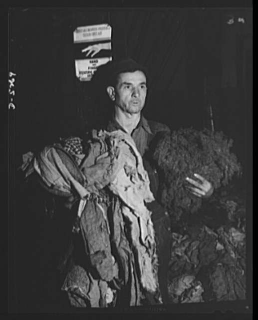 Salvage. Wool reclamation. A workman in an Eastern plant, reclaiming wool from old rags, holds on his right arm a collection of rags before they have passed through the rag-picking machine. On his left arm is wool fiber after being shredded from wool rags in a rag-picking machine