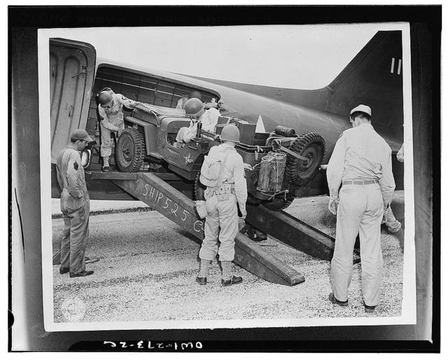 """San Antonio, Texas. From a position behind the """"front lines"""", the airborne troopers were rushed to the objective on a split-second schedule to deliver the first blow in a carefully-planned offensive. A jeep is being loaded into a plane as part of this problem"""
