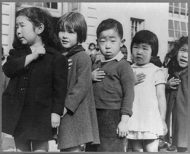 San Francisco, Calif., April 1942. First-graders, some of Japanese ancestry, at the Weill public school pledging allegience to the United States flag. The evacuees of Japanese ancestry will be housed in War relocation authority centers for the duration of the war