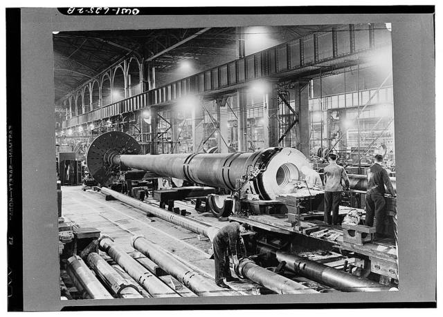 Scene in a gun plant where the big guns and shells are made, showing in the foreground a sixteen-inch naval gun being gauged after boring