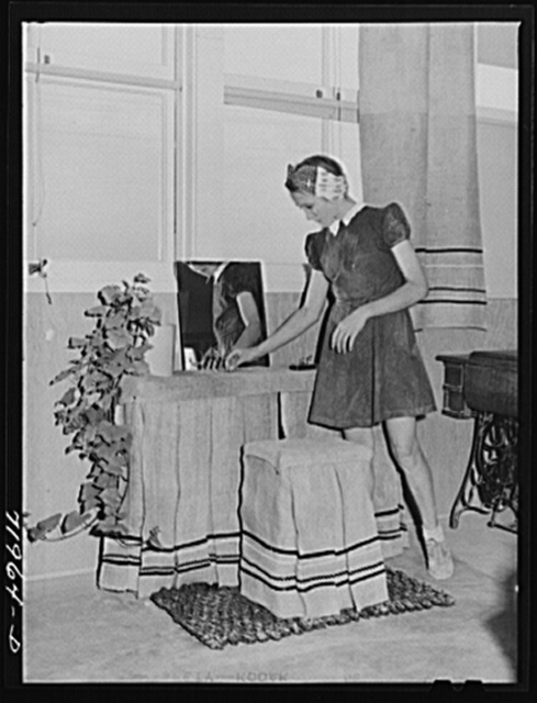 Schoolgirl with dressing table which the girls made of discarded vegetable crates and burlap. FSA (Farm Security Administration) farm workers' community, Eleven Mile Corner, Arizona