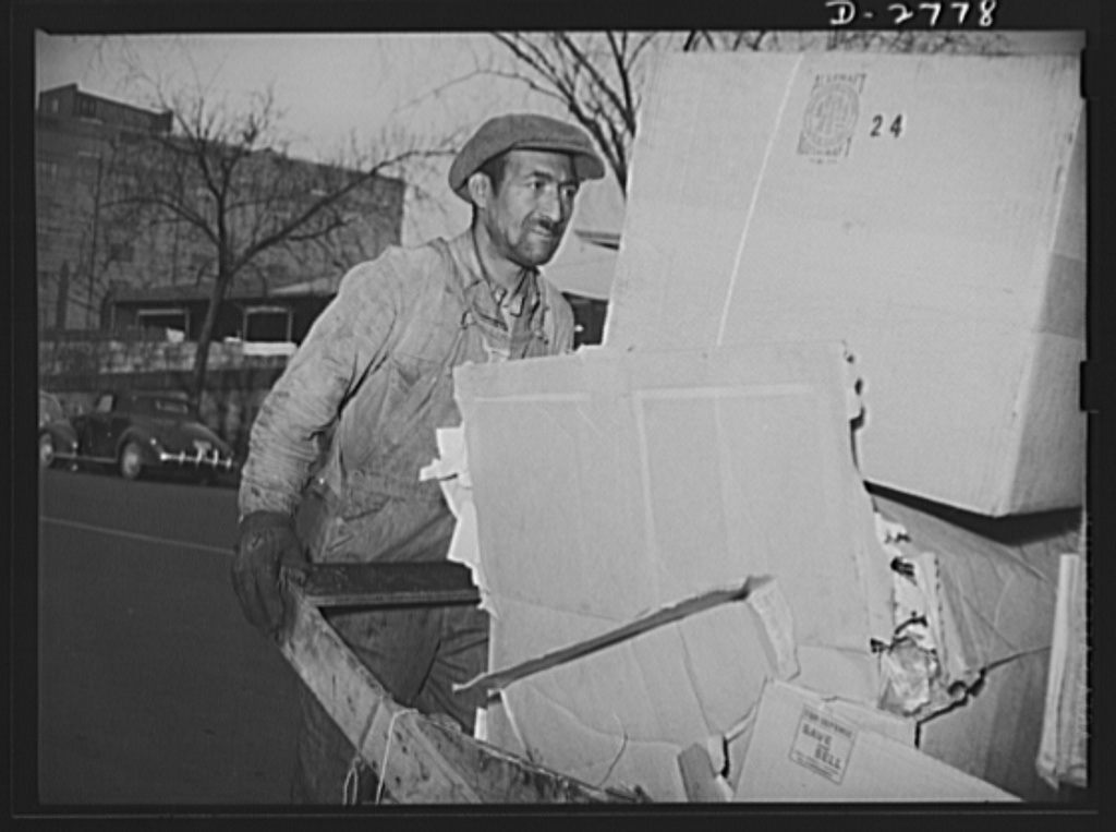 Scrap collection. Junk man pushing his cart loaded with a day's pickings on his way to sell the paper, cardboard and rags to a large scrap dealer. Shapiro Company, Baltimore, Maryland
