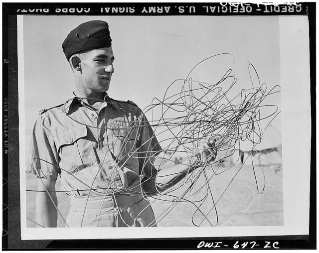 Sergeant C.M. Battleship of Sydney, Australia, leader of a RAF (Royal Air Force) attack which destroyed six Junker 52s and damaged others at the El Aden airdrome, examinig some of the telephone wire which was draped from the oil coolers, wireless  masts, tail, and rudder if his plane when he returned to the base. Flying low over the road, he cracked through enemy telephone wires