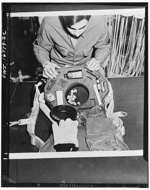Sergeant Tony Gaudiello, of Uniontown, Pennsylvania, somewhere in the European war theater, inspecting the contents of the kit which fits into the back pad of a parachute. It contains, among other things, concentrated food, emergency ration, a frying pan, knife, lighter, compass, bullets, gloves, and insecticide in a compact form