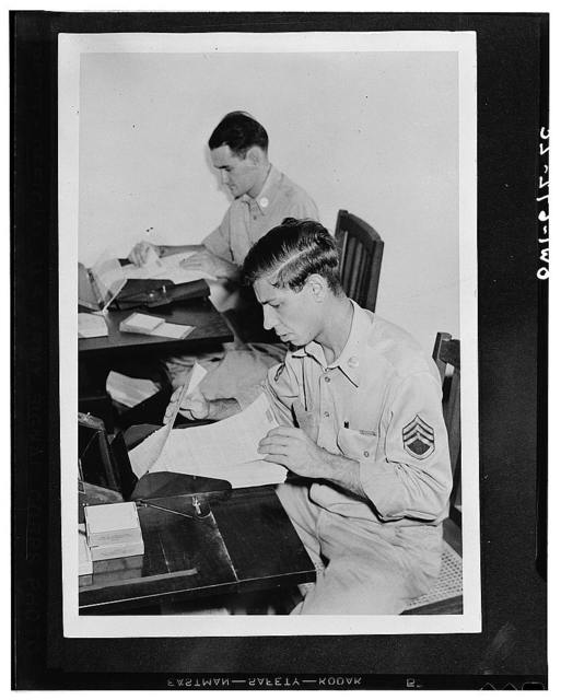 Sergeants Paul Busick of Baltimore, Maryland, and Frederick Garlick of Plainfield, New Jersey, somewhere in India feeding the hand- and typewitten V-letters into the Recordak camera which records them on film