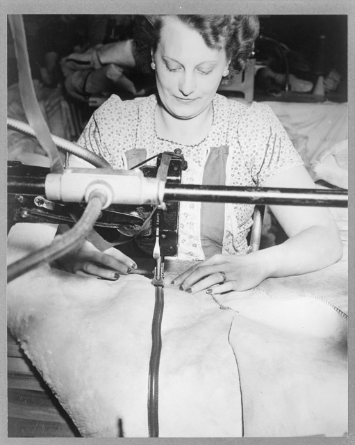 Sewing leather facing over seam of a coat, for the Armed forces(?), at the Aero Leather Coat Company / Gruber.