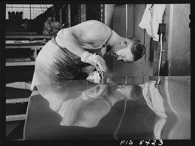 Sheffield, Alabama. Reynolds Alloys Company. Workman gauging the thickness of a sheet of aluminum which he is rolling