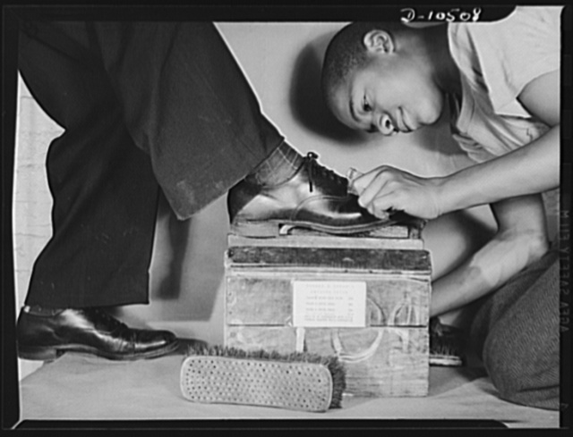 Shining up an administrator. With ceiling prices listed on his shoe box, Howard Rae Lynch, fourteen, polishes the shoes of Office of Price Administration (OPA) Leon Henderson