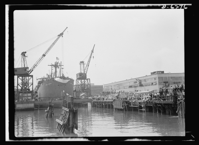 Ship launching in Portland, Maine. Spectators crowded the docks when Ocean Seaman, one of five lend-lease cargo-carrying ships built for Britain, was christened at a Maine shipyard on August 16, 1942. The vessel was completed forty-eight days after its keel was laid