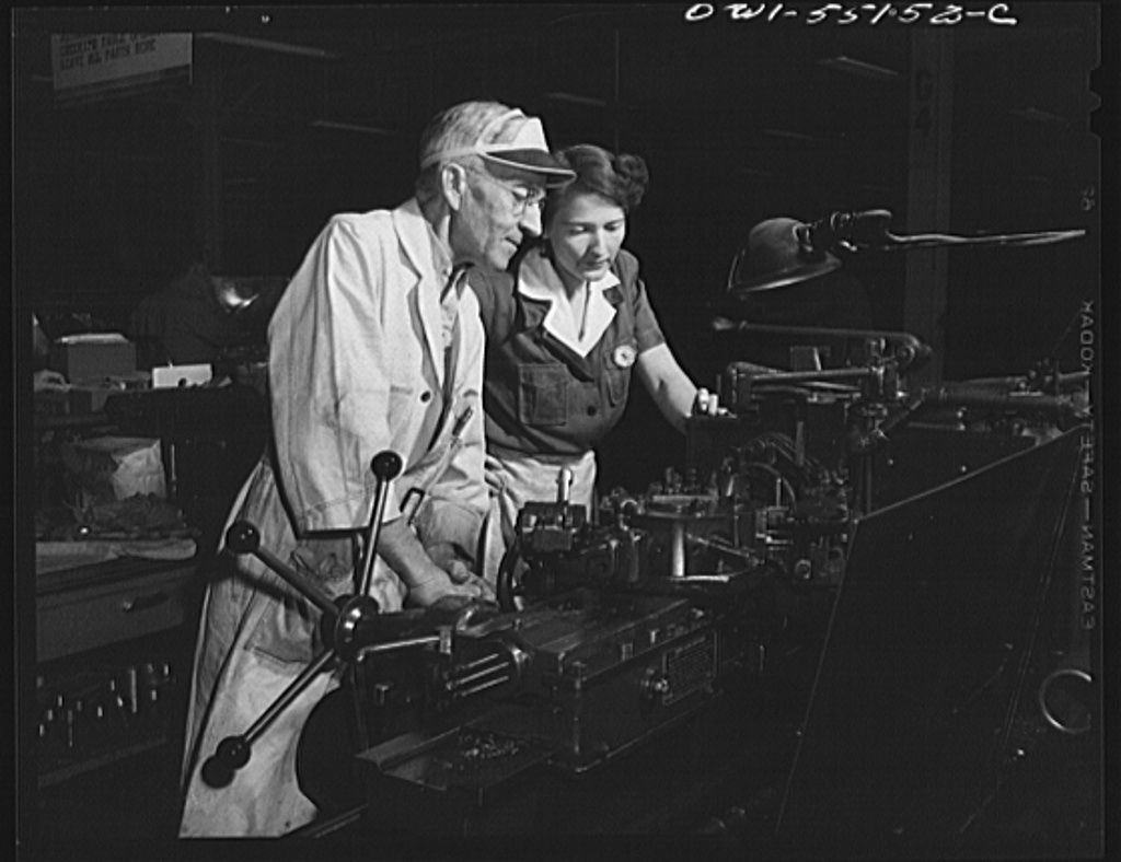 Skilled machinists are vital to the war production program. Here a woman employee operates a turret lathe under the close supervision of a skilled machinist in North American's modern machine shop