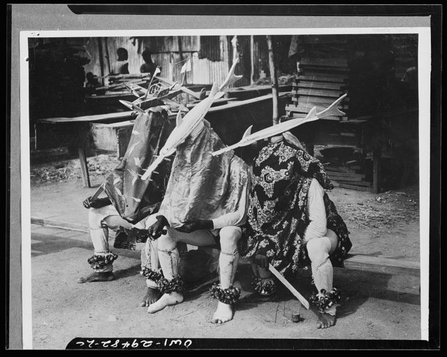Somewhere in Central Africa. Modern science takes its place beside old time African fetishes, as the witch doctors rest between dances. The fish are typical examples of customary ju-ju that has come down through ages of the Dark Continent's history, and the American-built RAF (Royal Air Force) Consolidated Liberator is a sample of the head masks used by the dancers who have streamlined imagination and appreciate the white man's stronger ju-ju