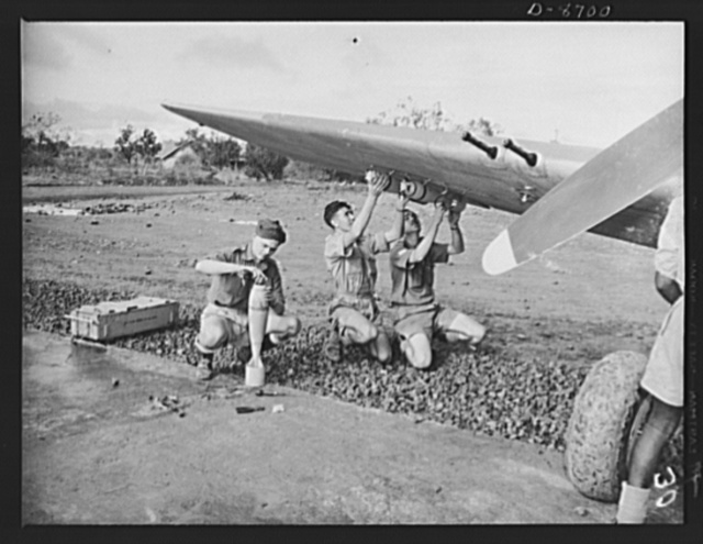 """Somewhere in Eastern India. Royal Air Force men are putting bombs on legs of a """"Mohawk."""" These excellent fighters carry six bombs as well as six machine guns"""